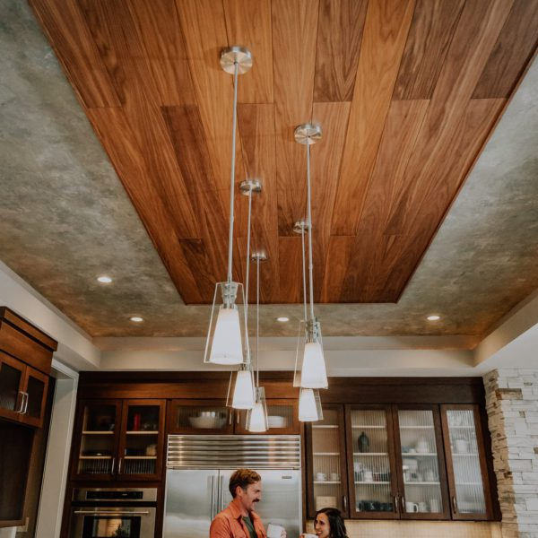 Walnut acoustic wood planks featured on a kitchen ceiling and a couple enjoying coffee together.