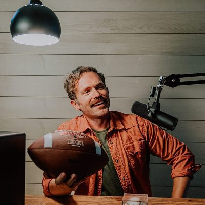 Man holds football in his podcast room in front of maple wood wall.