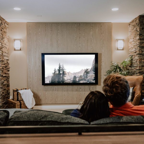 A couple enjoying a movie in their media room with an acoustic wood wall, stone fireplace, television, and a leather chair.
