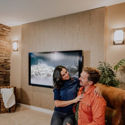 A couple in their media room with an acoustic wood wall, stone fireplace, television, and a leather chair.