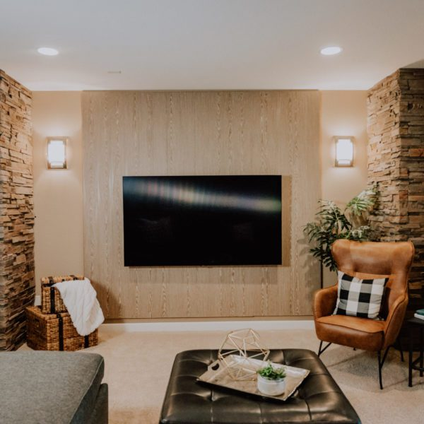 Media room with an acoustic wood wall, television, and a leather chair.